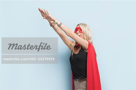 Young woman in superhero outfit pretending to leap in the air against light blue background Stock Photo - Premium Royalty-Free, Image code: 693-06379993