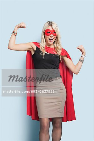 Portrait of excited young blond woman in superhero costume flexing arms over light blue background Stock Photo - Premium Royalty-Free, Image code: 693-06379994