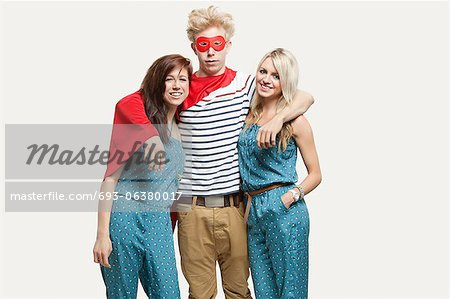 Portrait of young man in superhero costume and women wearing jumpsuits standing together against gray background Stock Photo - Premium Royalty-Free, Image code: 693-06380017