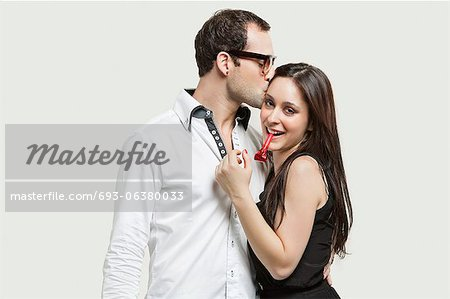 Young couple with party puffer against gray background Stock Photo - Premium Royalty-Free, Image code: 693-06380033