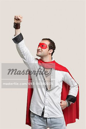 Young man in superhero costume standing against gray background Stock Photo - Premium Royalty-Free, Image code: 693-06380036