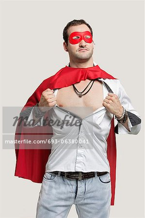 Young man in superhero costume standing against gray background Stock Photo - Premium Royalty-Free, Image code: 693-06380041