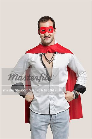 Portrait of young man in superhero costume with hands on hip standing against gray background Stock Photo - Premium Royalty-Free, Image code: 693-06380042