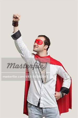 Young man in superhero costume with hand raised against gray background Stock Photo - Premium Royalty-Free, Image code: 693-06380043