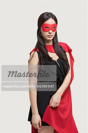 Portrait of young woman in superhero costume standing against gray background Stock Photo - Premium Royalty-Free, Image code: 693-06380047