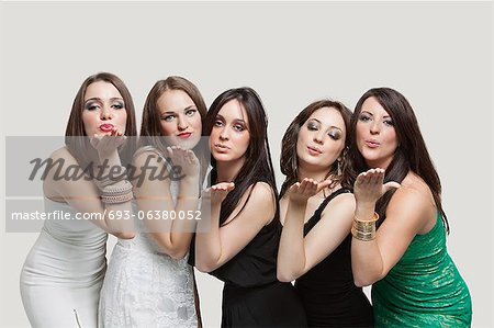 Five young women blowing kisses over gray background Stock Photo - Premium Royalty-Free, Image code: 693-06380052