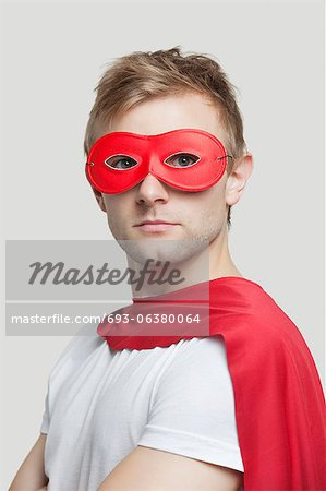 Portrait of young man wearing superhero costume against gray background Stock Photo - Premium Royalty-Free, Image code: 693-06380064