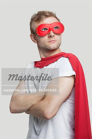 Young man in red superhero costume looking up over gray background Stock Photo - Premium Royalty-Free, Image code: 693-06380065