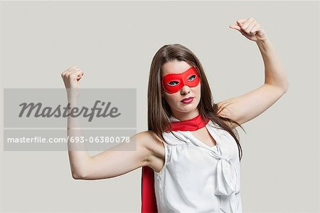 Portrait of a young woman in super hero costume flexing muscles over gray background Stock Photo - Premium Royalty-Free, Image code: 693-06380078