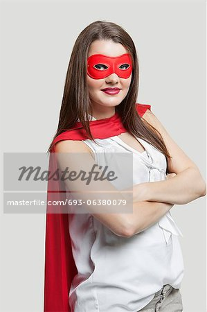 Portrait of a young woman in super hero costume over gray background Stock Photo - Premium Royalty-Free, Image code: 693-06380079