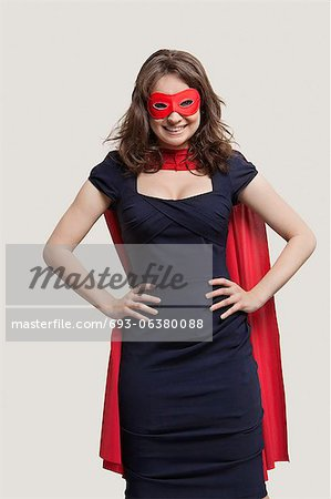 Portrait of a young woman in superhero costume over gray background Stock Photo - Premium Royalty-Free, Image code: 693-06380088