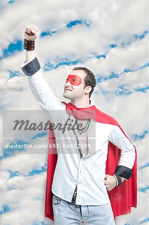 Young man in superhero costume with hand raised against cloudy sky Stock Photo - Premium Royalty-Free, Image code: 693-06403199