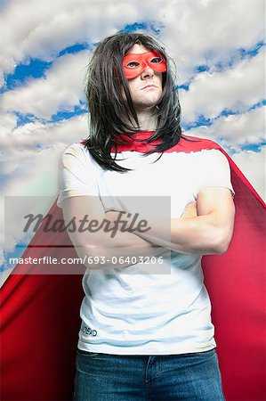 Young man in super hero costume with arms crossed against cloudy sky Stock Photo - Premium Royalty-Free, Image code: 693-06403206