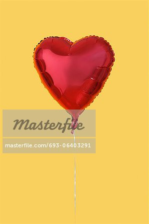 Red heart shaped balloon over yellow background Stock Photo - Premium Royalty-Free, Image code: 693-06403291