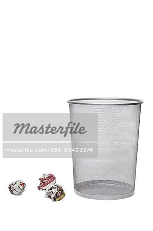 Crumpled papers next to empty wastebasket over white background Stock Photo - Premium Royalty-Free, Image code: 693-06403374