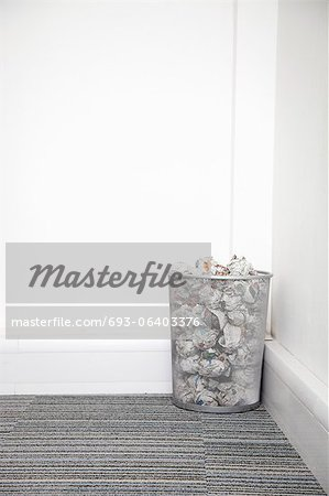 Wastebasket full of crumpled paper in corner against white wall Stock Photo - Premium Royalty-Free, Image code: 693-06403376