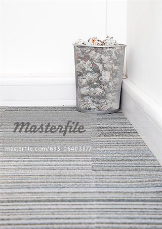 Wastebasket full of crumpled paper in corner on carpet floor in room Stock Photo - Premium Royalty-Free, Image code: 693-06403377