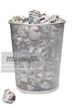 Wastepaper basket with papers lying over white background Stock Photo - Premium Royalty-Free, Image code: 693-06403379