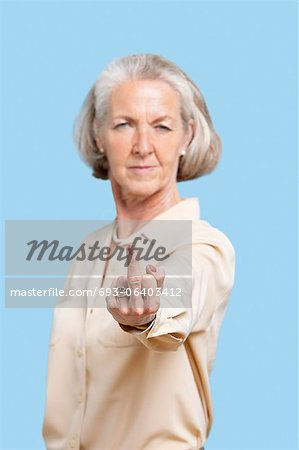 Portrait of senior woman in casuals making rebellious gesture against blue background Stock Photo - Premium Royalty-Free, Image code: 693-06403412