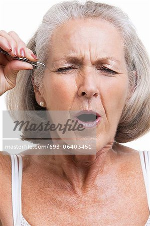 Senior woman tweezing eyebrows against white background Stock Photo - Premium Royalty-Free, Image code: 693-06403451