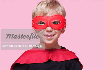 Portrait of a happy boy in superhero costume over pink background Stock Photo - Premium Royalty-Free, Image code: 693-06403547