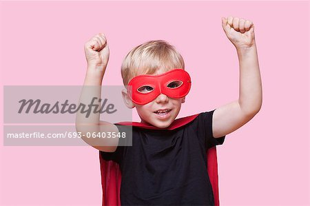 Young boy dressed in superhero costume with arms raised over pink background Stock Photo - Premium Royalty-Free, Image code: 693-06403548