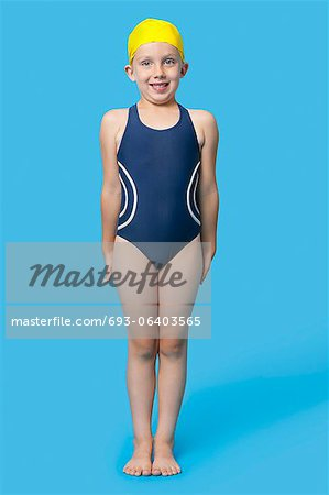 Portrait of a happy young girl in swimming costumes over blue background Stock Photo - Premium Royalty-Free, Image code: 693-06403565