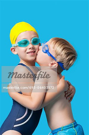 Young siblings in swimwear embracing and kissing over blue background Stock Photo - Premium Royalty-Free, Image code: 693-06403572