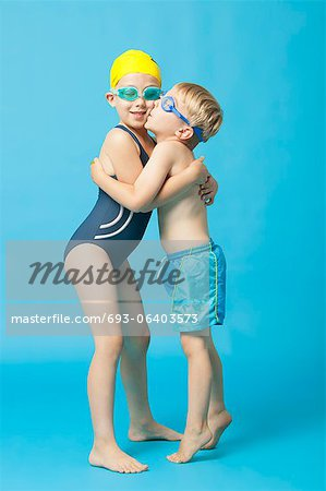 Young siblings in swimwear embracing and kissing over blue background Stock Photo - Premium Royalty-Free, Image code: 693-06403573