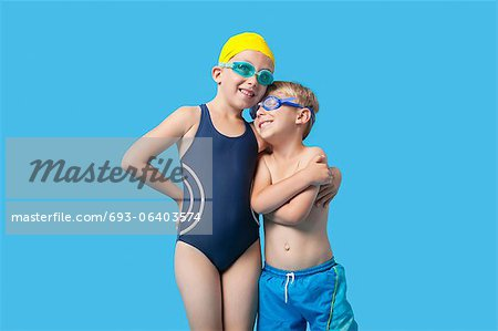 Happy young siblings in swimwear with arm around over blue background Stock Photo - Premium Royalty-Free, Image code: 693-06403574
