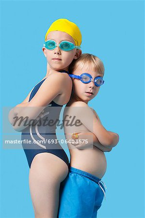 Profile shot of young boy and girl in swimwear standing back to back over blue background Stock Photo - Premium Royalty-Free, Image code: 693-06403575
