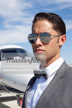 Handsome young men wearing sunglasses with private plane in background Stock Photo - Premium Royalty-Free, Image code: 693-06435748