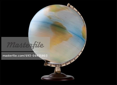 Close-up of spinning globe over black background Stock Photo - Premium Royalty-Free, Image code: 693-06435803