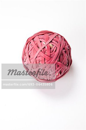 Close-up of rubber band ball over white background Stock Photo - Premium Royalty-Free, Image code: 693-06435806