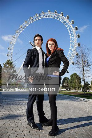 Portrait of confident young business couple standing together against London Eye, London, UK Stock Photo - Premium Royalty-Free, Image code: 693-06435875