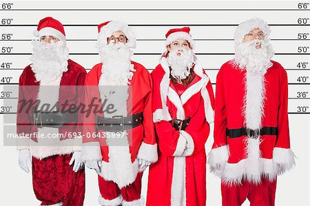People in Santa costume standing side by side against police lineup Stock Photo - Premium Royalty-Free, Image code: 693-06435897