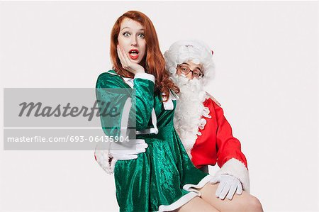 Portrait of Santa touching woman inappropriately against gray background Stock Photo - Premium Royalty-Free, Image code: 693-06435904