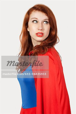 Young woman in superhero costume looking away against gray background Stock Photo - Premium Royalty-Free, Image code: 693-06435933