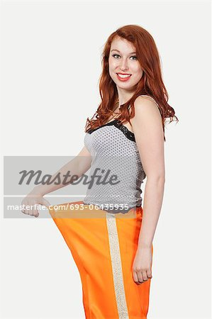 Portrait of young Caucasian woman oversized orange pants against gray background Stock Photo - Premium Royalty-Free, Image code: 693-06435935