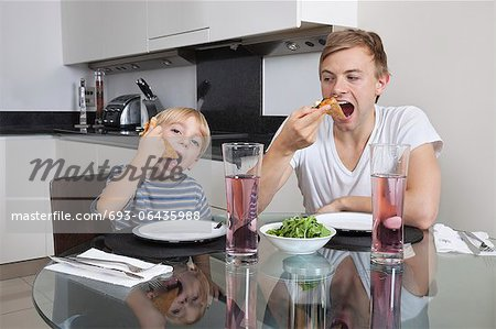 Father and son eating pizza at breakfast table Stock Photo - Premium Royalty-Free, Image code: 693-06435988