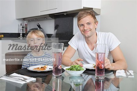 Portrait of father and son smiling at breakfast table Stock Photo - Premium Royalty-Free, Image code: 693-06435989