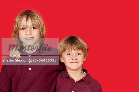 Portrait of two happy brothers against red background Stock Photo - Premium Royalty-Free, Image code: 693-06436025