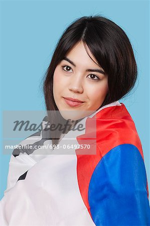Patriotic young woman wrapped in Korean flag over blue background Stock Photo - Premium Royalty-Free, Image code: 693-06497570