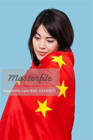 Patriotic young woman wrapped in Chinese flag over blue background Stock Photo - Premium Royalty-Free, Image code: 693-06497571