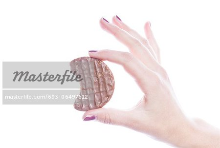 Detail shot of woman holding cookie over white background Stock Photo - Premium Royalty-Free, Image code: 693-06497612