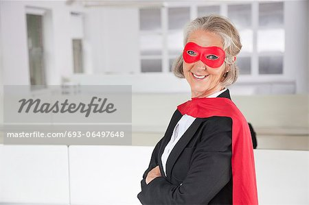 Portrait of smiling senior businesswoman in superhero costume in office Stock Photo - Premium Royalty-Free, Image code: 693-06497648