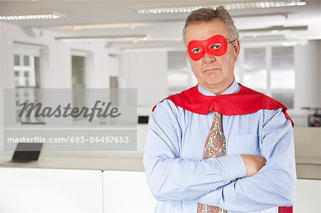 Portrait of serious businessman in superhero costume in office Stock Photo - Premium Royalty-Free, Image code: 693-06497653