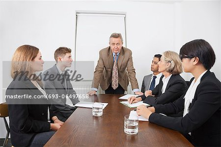 Multiethnic businesspeople at meeting in conference room Stock Photo - Premium Royalty-Free, Image code: 693-06497658