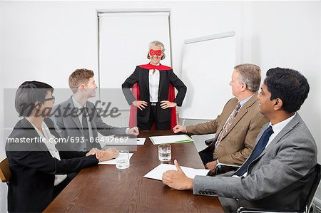 Business leader as superhero in front of colleagues at meeting in conference room Stock Photo - Premium Royalty-Free, Image code: 693-06497667