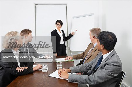 Young woman using whiteboard in business meeting Stock Photo - Premium Royalty-Free, Image code: 693-06497669